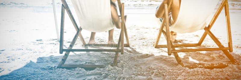 Lyckliga par som dricker coctailar, medan koppla av på deras solstolar royaltyfri bild