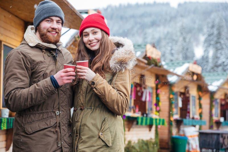 Lyckliga par som dricker kaffe på jul, marknadsför i bergsemesterort royaltyfri fotografi