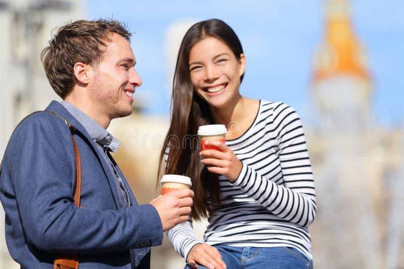 Lyckliga par som dricker kaffesamtal royaltyfri fotografi