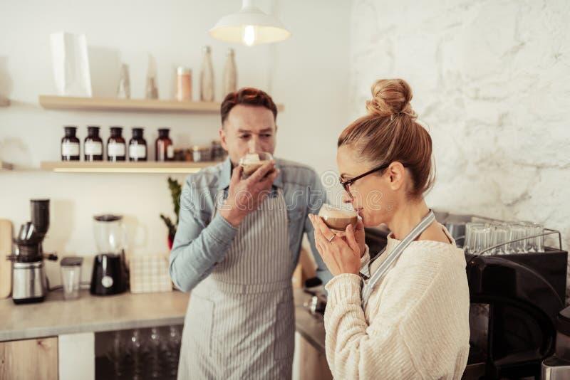 Lyckliga par som dricker nytt bryggat kaffe tillsammans arkivbilder
