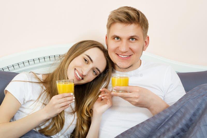 Lyckliga par som dricker orange fruktsaft, medan ligga i säng i sovrum i morgonen - sund livsstil och näringbegrepp arkivfoto