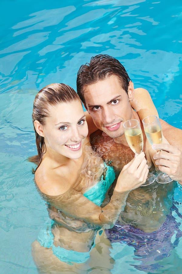 Lyckliga par som dricker vin i pöl royaltyfri bild