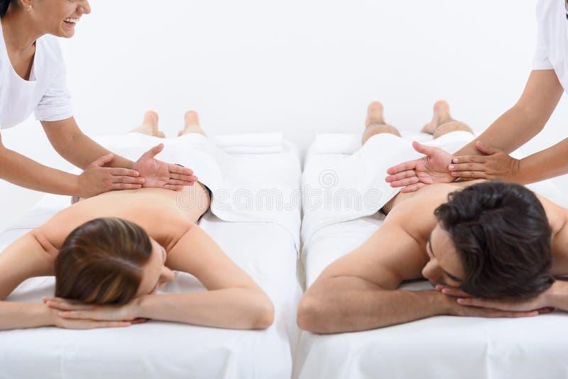 Lyckliga par som får massage på brunnsorten royaltyfria bilder