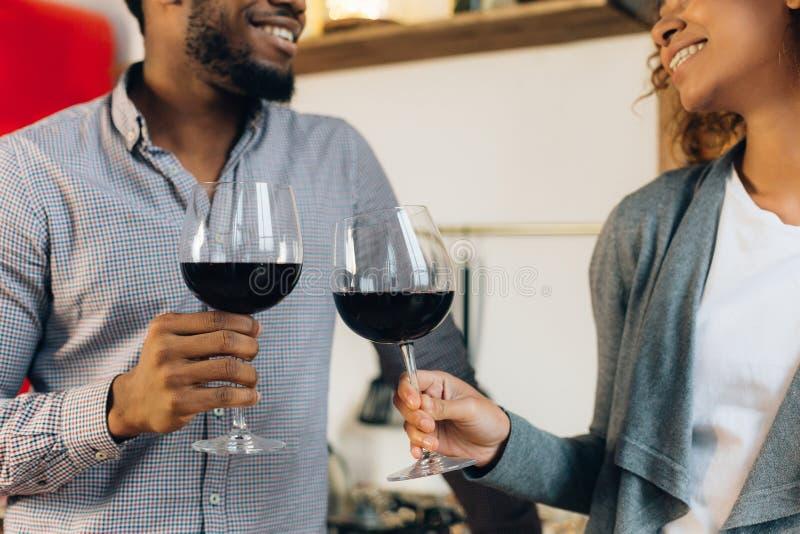 Lyckliga par som firar och hurrar med exponeringsglas av vin arkivfoton