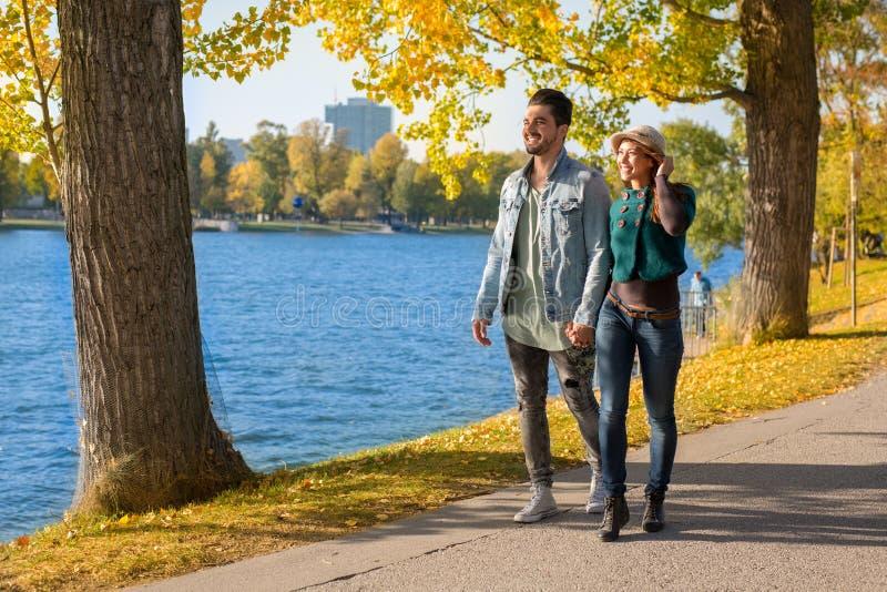 Lyckliga par som går i en parkera vid vattnet i höst royaltyfri bild
