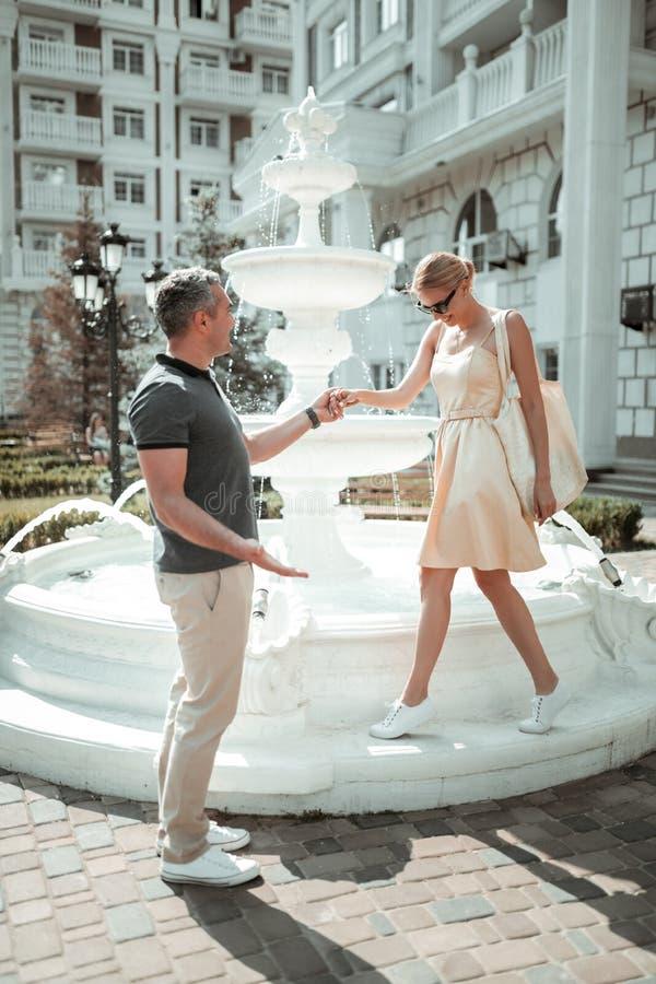 Lyckliga par som går nära den härliga springbrunnen royaltyfria bilder