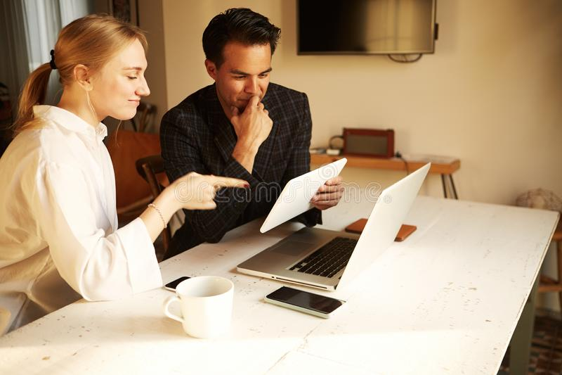 Lyckliga par som gör affären som arbetar tillsammans på det lilla kontoret på bärbara datorn royaltyfria foton