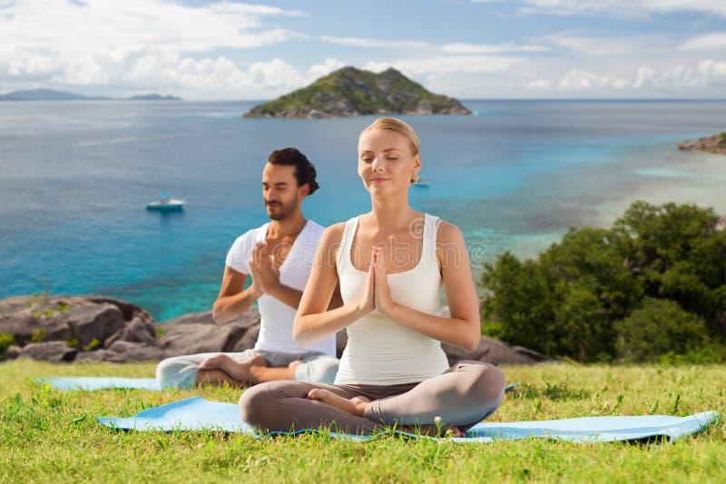Lyckliga par som gör yoga och utomhus mediterar royaltyfri foto