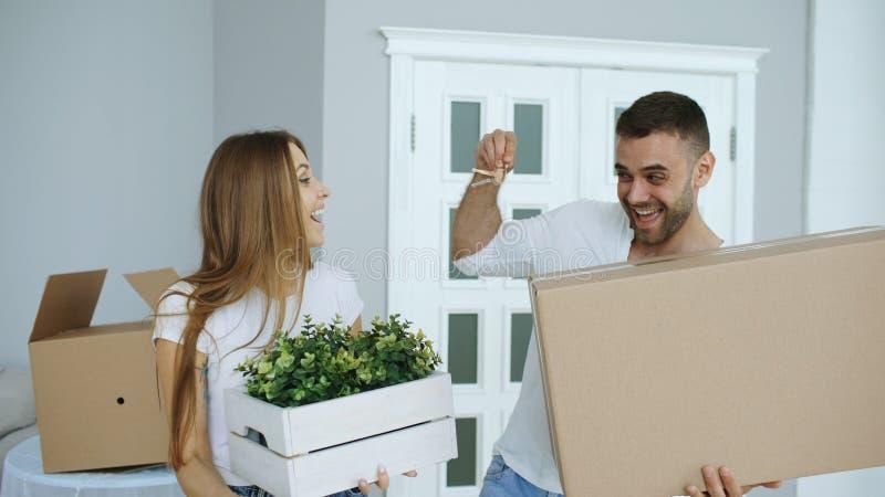 Lyckliga par som håller ögonen på deras nya hem- upphetsat Den unga mannen ger tangenter till hans flickvän och att kyssa henne arkivbild