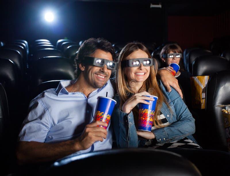 Lyckliga par som håller ögonen på filmen 3D i teater arkivfoton