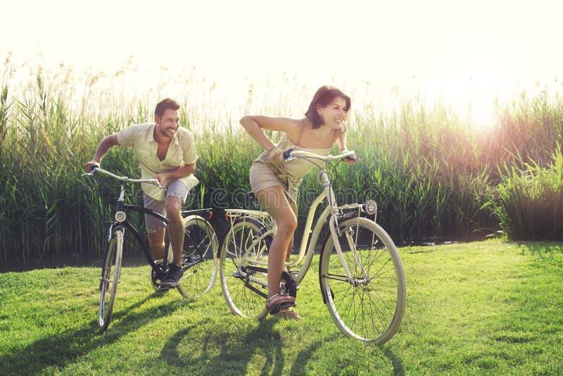 Lyckliga par som har ett cykellopp in i naturen royaltyfri bild