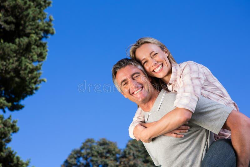 Lyckliga par som har gyckel i parkera arkivbild