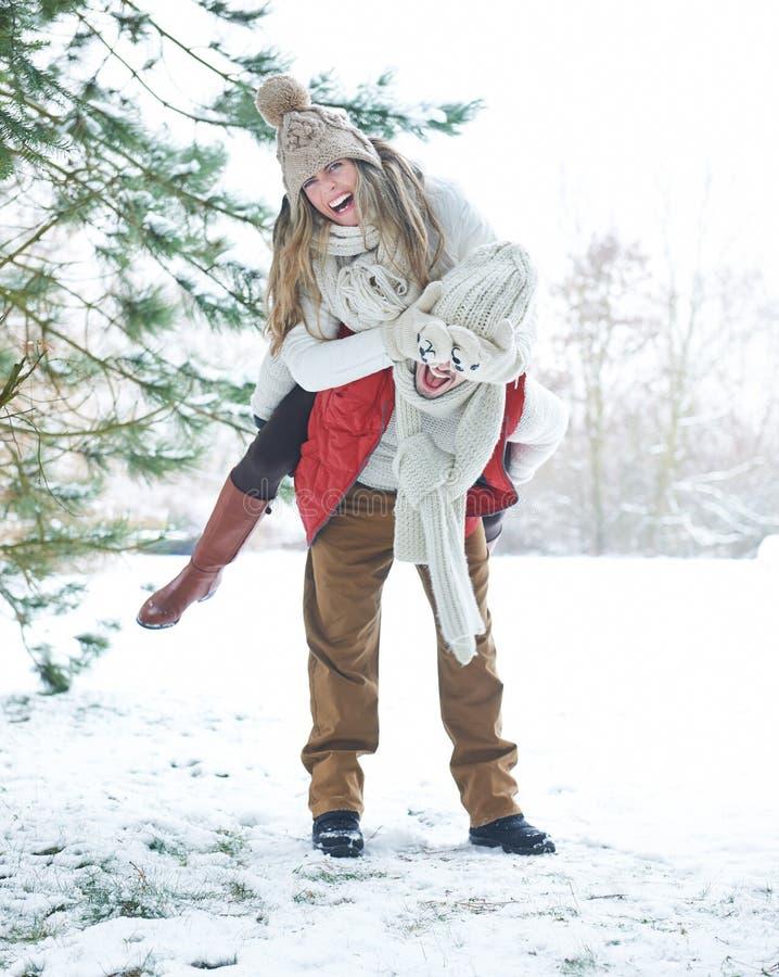 Lyckliga par som har gyckel i vinter royaltyfria foton