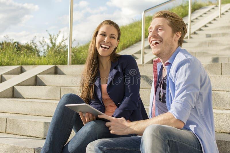 Lyckliga par som har gyckel med minnestavlaPC royaltyfria bilder