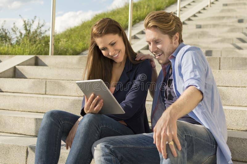 Lyckliga par som har gyckel med minnestavlaPC arkivfoto