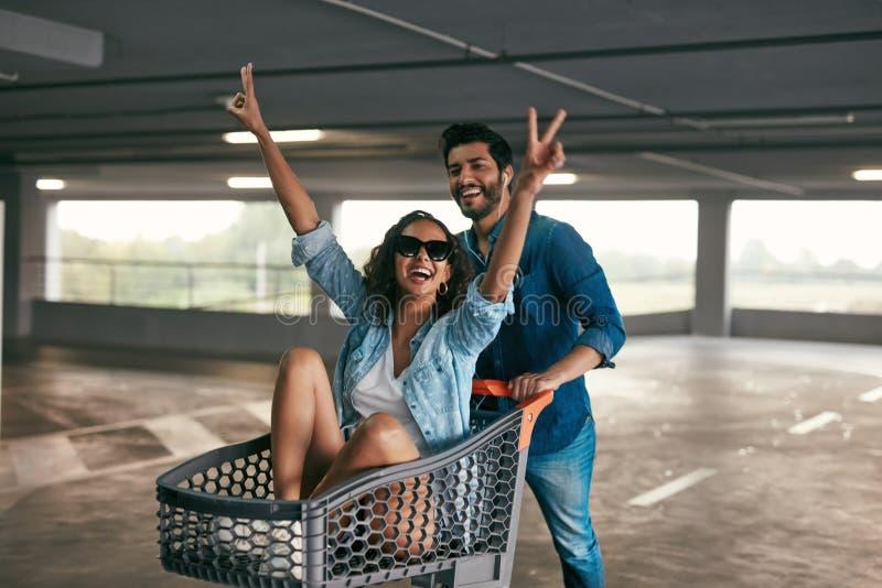 Lyckliga par som har gyckel med shoppingvagnen på galleriaparkering arkivfoton