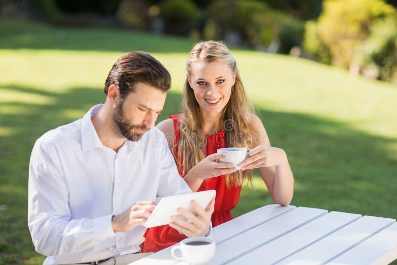 Lyckliga par som har kaffe och använder den digitala minnestavlan royaltyfri foto