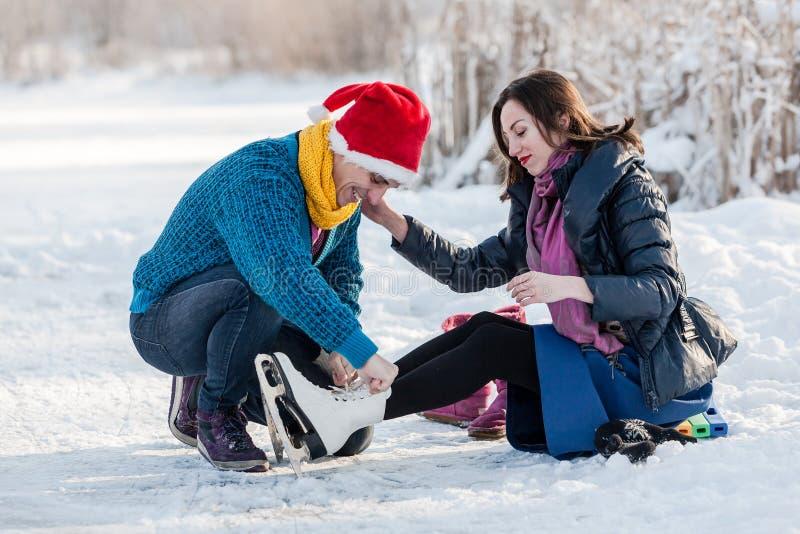 Lyckliga par som har rolig skridskoåkning på isbana utomhus royaltyfri foto