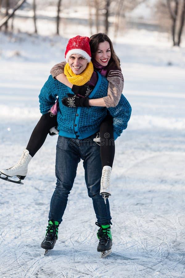 Lyckliga par som har rolig skridskoåkning på isbana utomhus arkivfoton