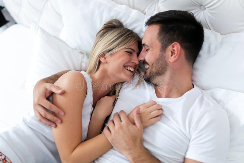 Lyckliga par som har romantiska tider i sovrum royaltyfri fotografi