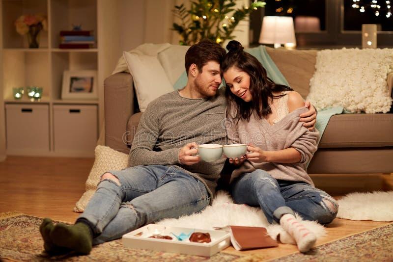 Lyckliga par som hemma dricker kakao royaltyfri foto