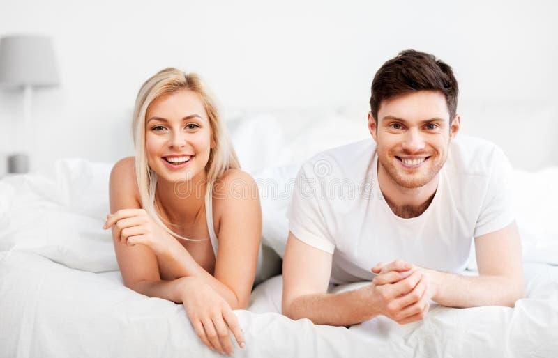 Lyckliga par som hemma ligger i säng arkivfoton