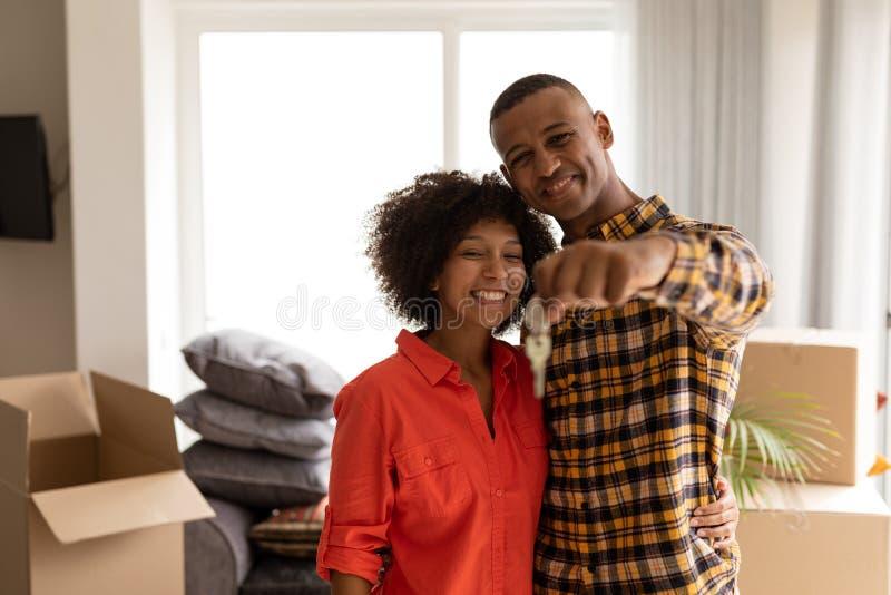Lyckliga par som hemma rymmer tangenter för nytt hus i vardagsrum arkivbild