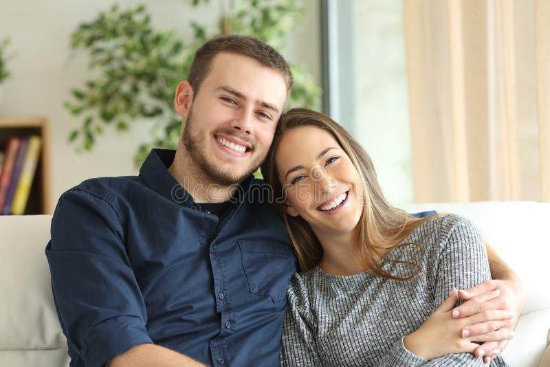 Lyckliga par som hemma ser kameran arkivbilder
