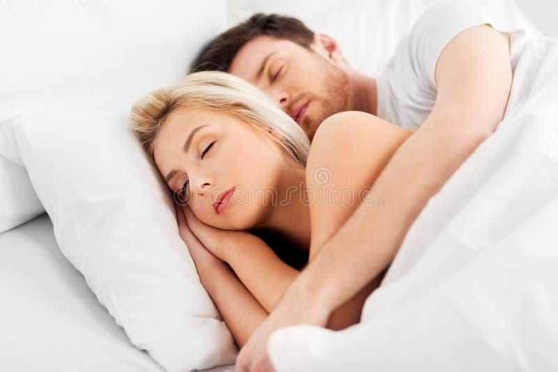 Lyckliga par som hemma sover i säng arkivfoton
