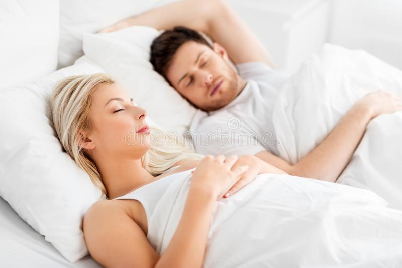 Lyckliga par som hemma sover i s?ng arkivbild