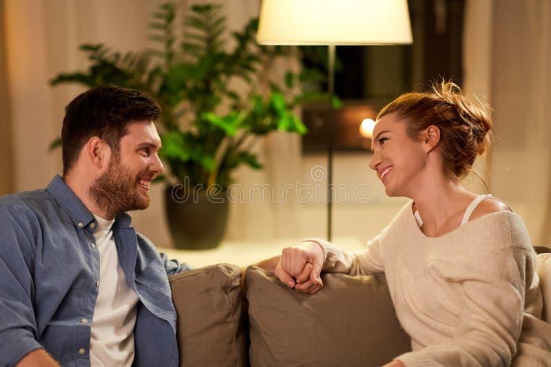Lyckliga par som hemma talar i afton royaltyfri fotografi