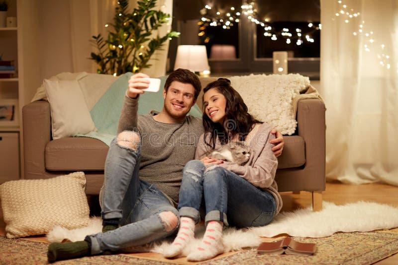 Lyckliga par som hemma tar selfie vid smartphonen royaltyfri foto