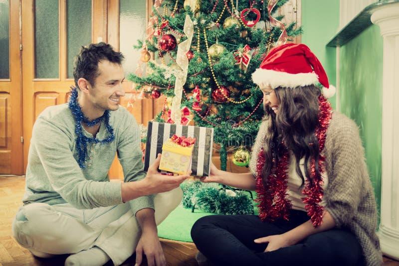 Lyckliga par som hemma utbyter gåvor vid julgranen royaltyfri fotografi