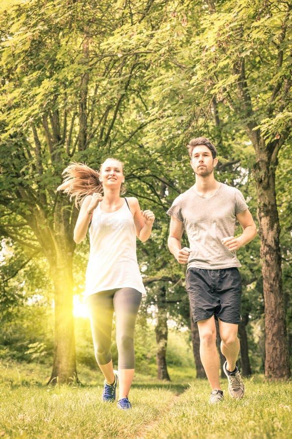 Lyckliga par som joggar och kör i parkera - konditionbegrepp royaltyfri bild