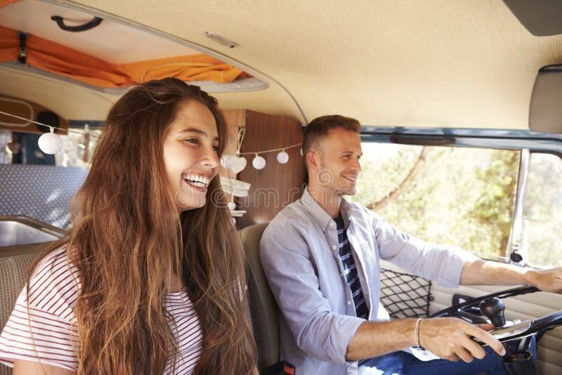 Lyckliga par som kör en campareskåpbil på en vägtur, semestrar arkivfoto