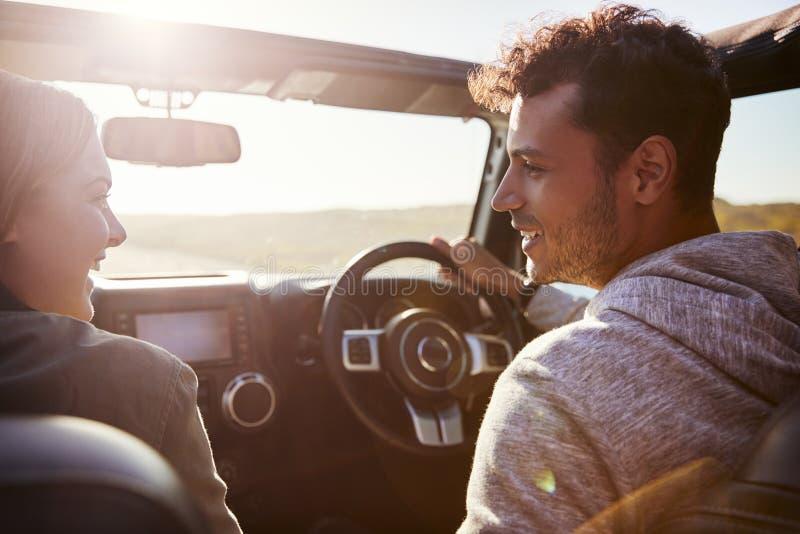 Lyckliga par som kör i bil med den öppna soltaket, passagerare POV royaltyfria foton