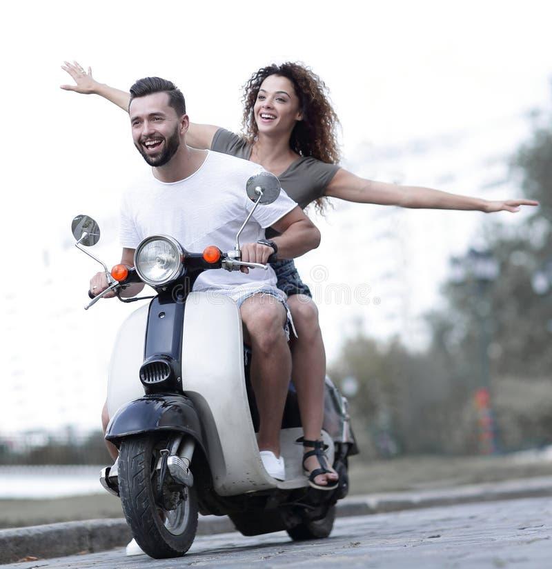 Lyckliga par som kör sparkcykeln som är upphetsad på sommarferier, semestrar royaltyfri bild