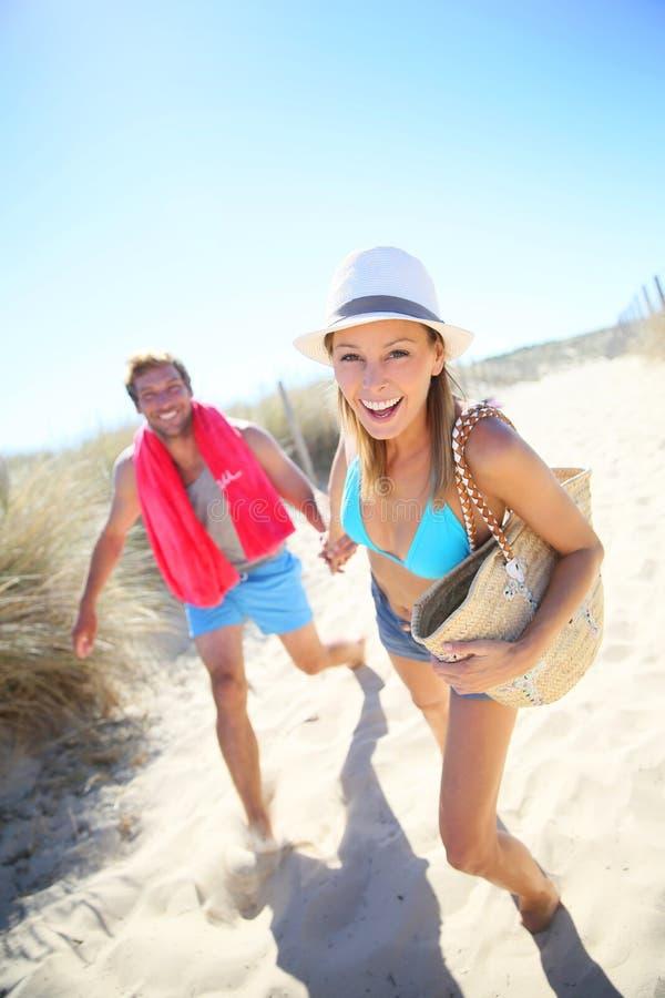 Lyckliga par som kör till stranden royaltyfri fotografi