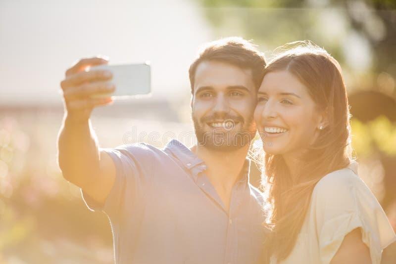 Lyckliga par som klickar selfie med den smarta telefonen arkivbild