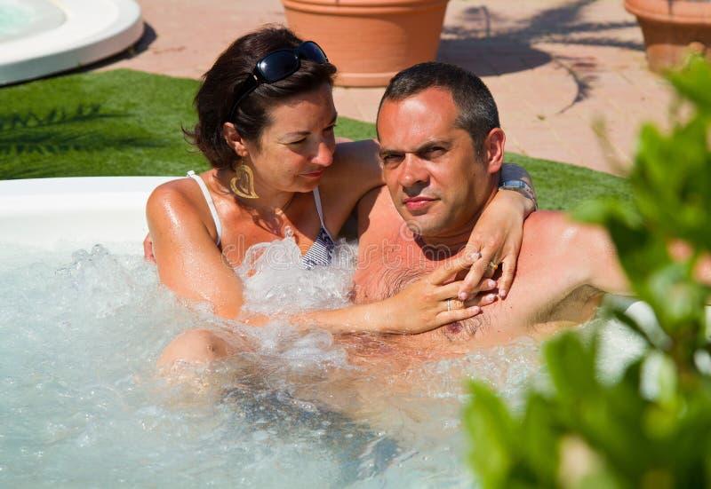Lyckliga par som kopplar av i varmt, badar arkivfoto