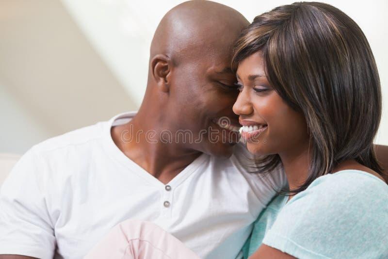 Lyckliga par som kopplar av på soffan royaltyfria bilder
