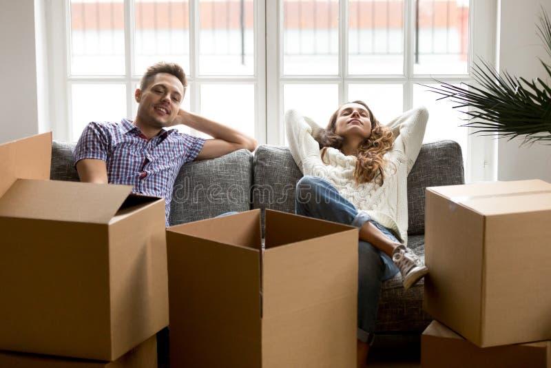 Lyckliga par som kopplar av på soffan efter nytt hem för inflyttning fotografering för bildbyråer