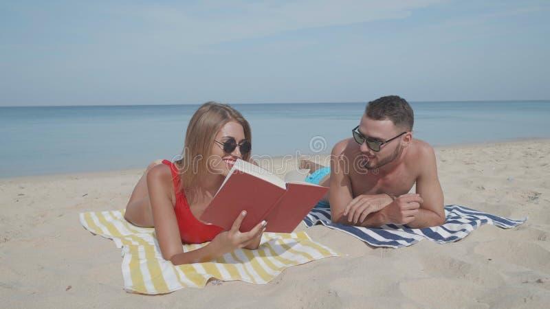 Lyckliga par som kopplar av på stranden royaltyfria bilder