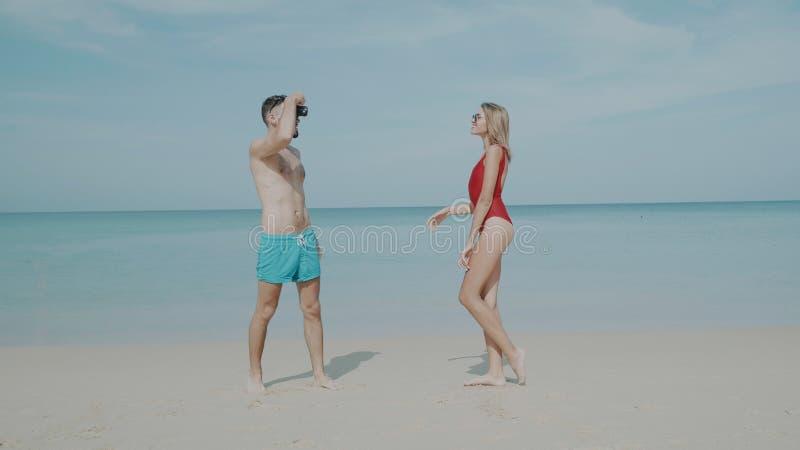 Lyckliga par som kopplar av på stranden arkivbilder