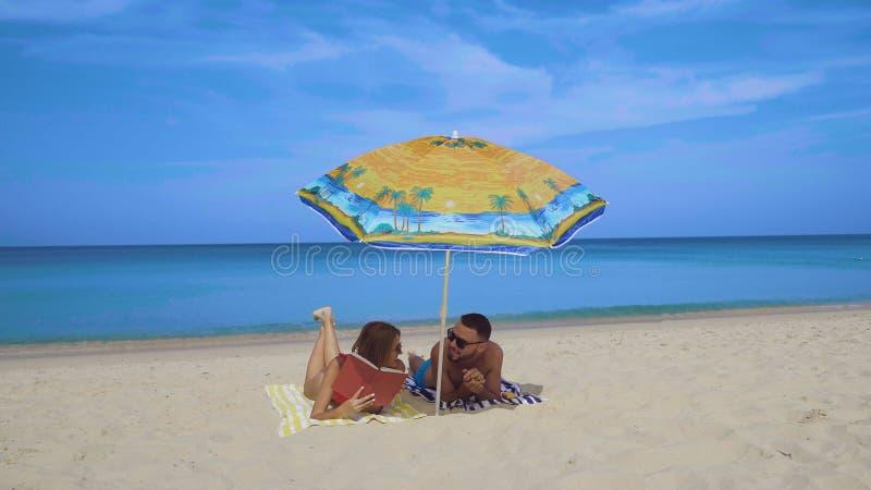 Lyckliga par som kopplar av på stranden arkivfoton