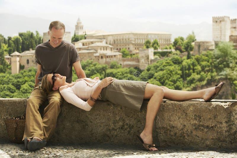 Lyckliga par som kopplar av på väggen arkivbilder