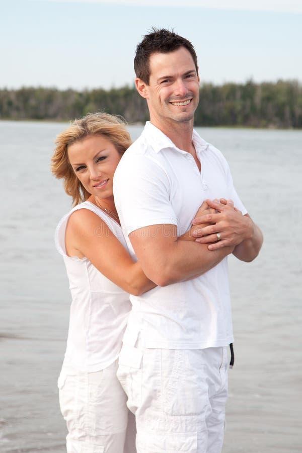 Lyckliga par som kopplar av vid havet royaltyfri bild