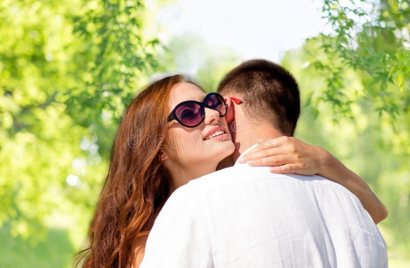 Lyckliga par som kramar över grön naturlig bakgrund arkivfoton
