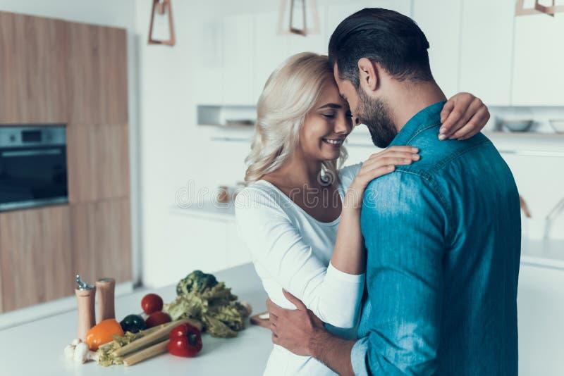 Lyckliga par som kramar i kök Romantiskt förhållande arkivfoton