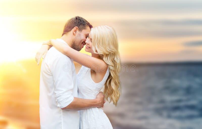 Lyckliga par som kramar och kysser på sommarstranden royaltyfria bilder
